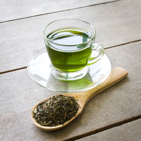 cup of green tea and spoon of dried green tea leaves on wooden background photo