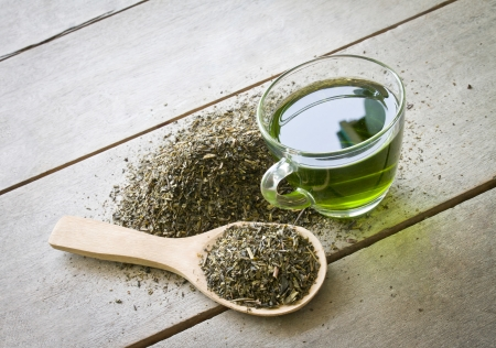 cup of green tea and spoon of dried green tea leaves on wooden background Banque d'images