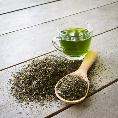 the green background: cup of green tea and spoon of dried green tea leaves on wooden background Stock Photo