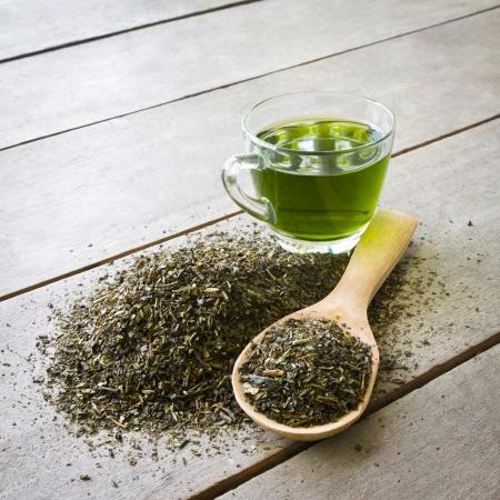 hojas de te: taza de t? verde y una cuchara de t? verde de hojas secas en el fondo de madera Foto de archivo
