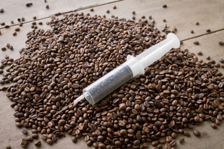 addictive drinking: coffee seed in syringe, mean to caffeine addiction Stock Photo