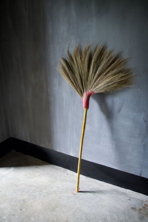 slovenly: Old broom or besom on the gray wall Stock Photo