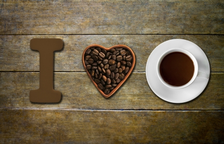 Heart shape made from coffee beans with a  cup of coffee, spelling I love coffee photo