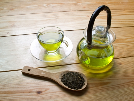 cup of green tea with scoop and tea pot on wooden background photo