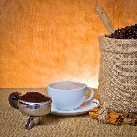 set of coffee, cup of coffee,ground coffee in portafilter,cinnamon, star anise photo