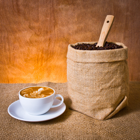 cafe latte and coffee beans in burlap photo