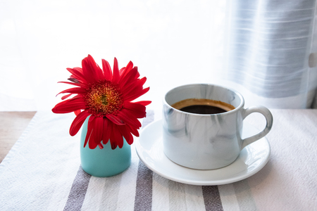 cup of coffee with flower in coffee shop
