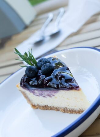 Blueberry Cheese cake in white dish on wooden table Banco de Imagens