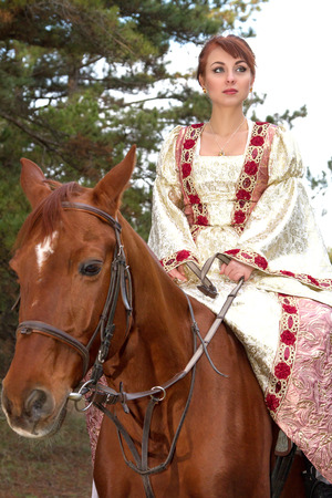 a beautiful girl in antique dress on horseback photo