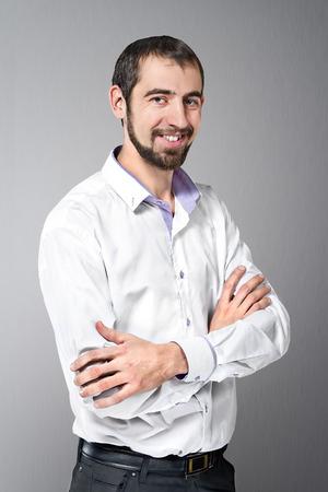 beau jeune homme: Portrait d'un jeune homme debout, les bras crois�s contre beau fond gris Banque d'images