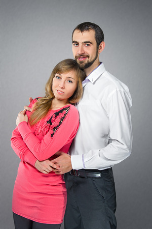 Young embracing couple in love posing at studiot photo
