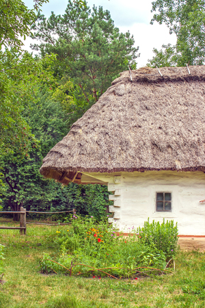 wooden hut: a landscape clay and wooden hut thatched Ukrainian Stock Photo