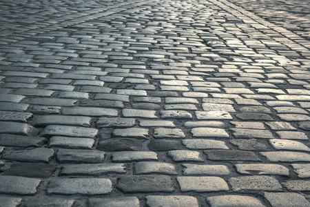 empedrado: imagen de fondo de la antigua carretera pavimentada con piedras de granito Foto de archivo