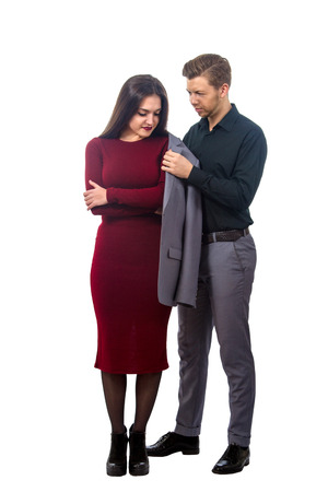 at tact: image of a young man puts his jacket on a girl in a red dress Stock Photo