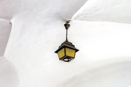 the image of a wrought lantern under the white vault of the castle