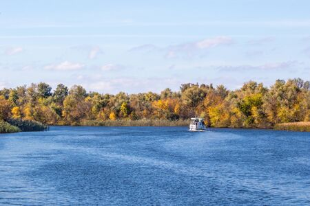image of a little white steamboat walking along a large autumn river