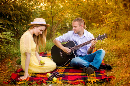 image of a young man playing guitar for a girl in the park