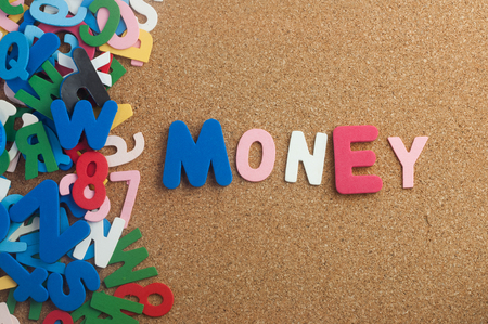 Colourful word money with cork board as background Stock Photo