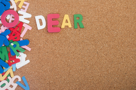 unsolicited: Colourful word dear with background cork board Stock Photo