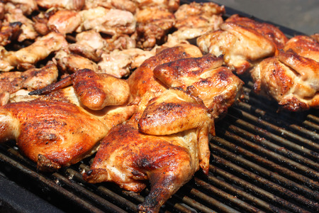 Grilled barbecue chicken on open grill Imagens