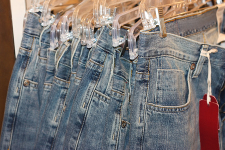 Row of jeans hangind in the store photo