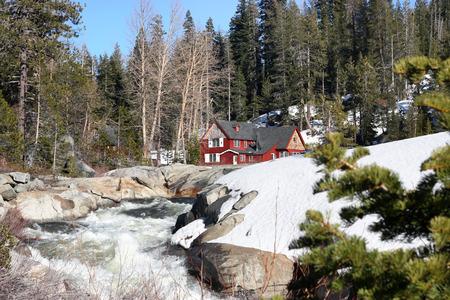 Beautiful cabin in snow near waterfall