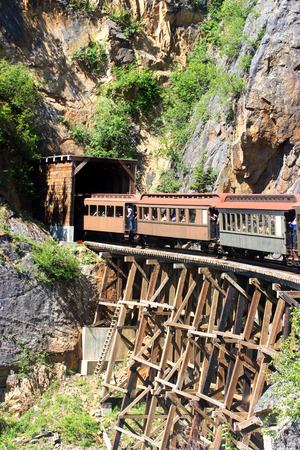 Train entering a tunnel through old bridge photo
