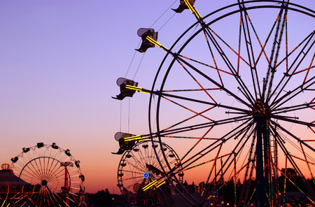 roller: Silhouettes of carnival rides under sunset Stock Photo