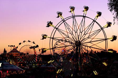 Silhouettes of carnival rides under sunset Archivio Fotografico