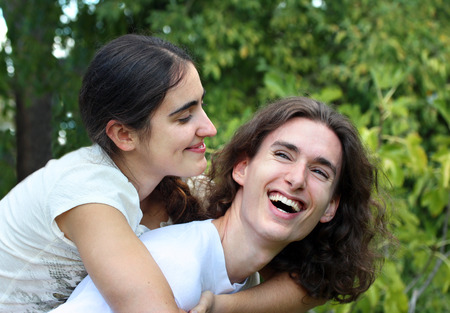 people portraits: Young happy couple laughing outdoors