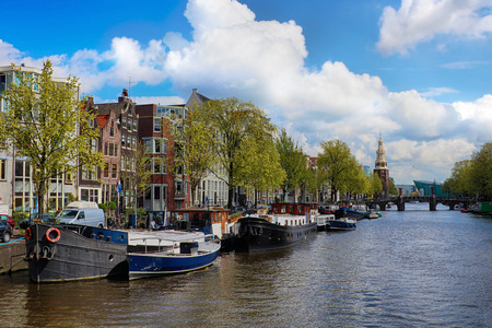 westerkerk: Amsterdam canal with boats and typical dutch houses.