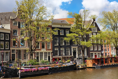 Amsterdam canal with boats and typical dutch houses.