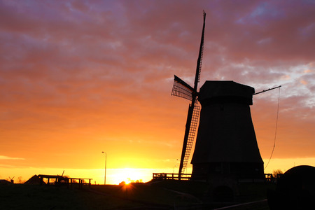 Silhouette of traditional windmill in Netherlands during sunrise
