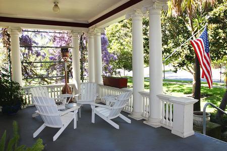 julio: Americana que cuelga la bandera en el porche de la casa