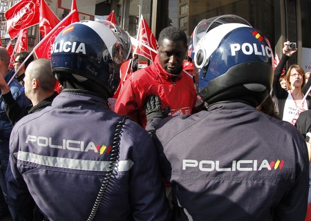 Palma de Mallorca, Spain - March 29, 2012 - Police officers push a black skinned demonstrator during a general strike protest against cutting on social services in Spain