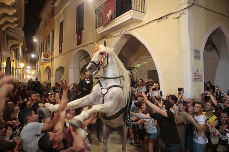 revellers: A rider rears up on his horse while surrounded by a cheering crowd during the traditional Fiesta of San Joan (Saint John) in downtown Ciutadella, Balearic Island of Menorca, Spain June 24, 2016. The riders of the horses are representatives of ancient Ciut