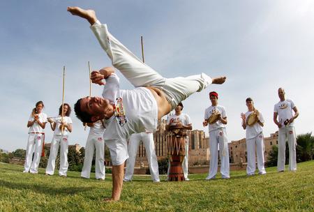 BACKFLIP: Palma de Mallorca, Spain - May 14, 2011 - Capoeira dancers training outdoors during sunny journeys in the Spanish island of Mallorca Editorial