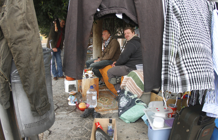 February 1, 2013 - homeless people and their belongs living on a bench in a street in Palma de Mallorca