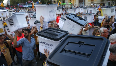 Barcelona, Spain - October 1, 2018 - People raise their hands and shout slogans while carrying the voting ballots used the last year banned independence referendum during the 1st October protests in Barcelona to claim the independence of Catalonia to Spai Redakční
