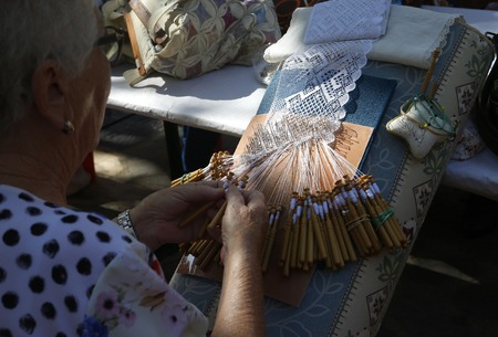 Esporles Mallorca, Spain - October 7, 2018 - Bobbin lace weaver woman showing her traditional handmade technique during a local fair in the village of Esporles in the Spanish island of Mallorca.