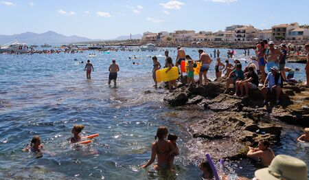 Can Picafort, Mallorca / Spain - August 15, 2019: People enjoy a traditional rubber ducks throw in the water in the beach of can picafort in the island of Mallorca, until two decades ago, live animals were used during this many decades tradition.