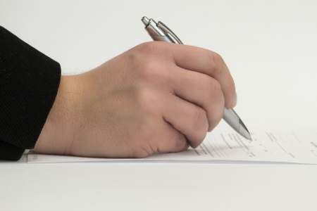 missive: hand with a pencil while signing contract