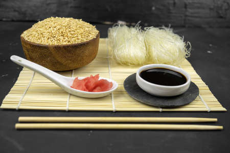 brown rice in a wooden bowl, asian kitchen background with bamboo mat, chopsticks, soy sauce, pickled ginger and glass rice noodles on black background Banco de Imagens