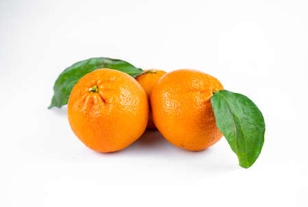 Ripe fresh juicy tangerines with leaves on white background