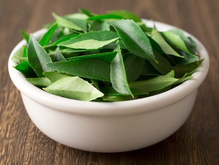 close up of a bowl of fresh indian curry leaves Stockfoto