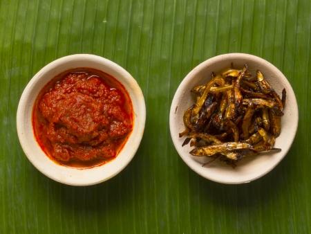 close up of bowls of fried anchovies and sambal chili photo