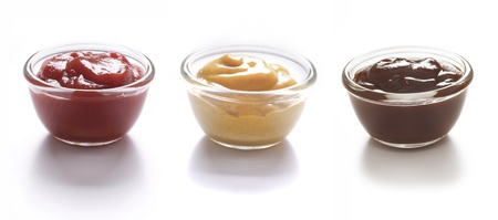 close up of bowls of tomato ketchup and mustard and barbecue sauce photo