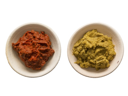 close up of bowls of red and yellow indian curry paste isolated