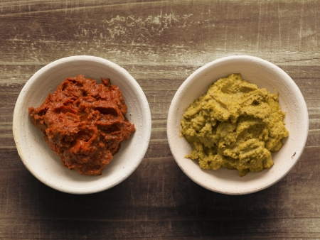 close up of bowls of red and yellow indian curry paste photo