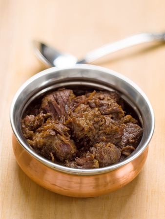 close up of a bowl of spicy beef rendang photo